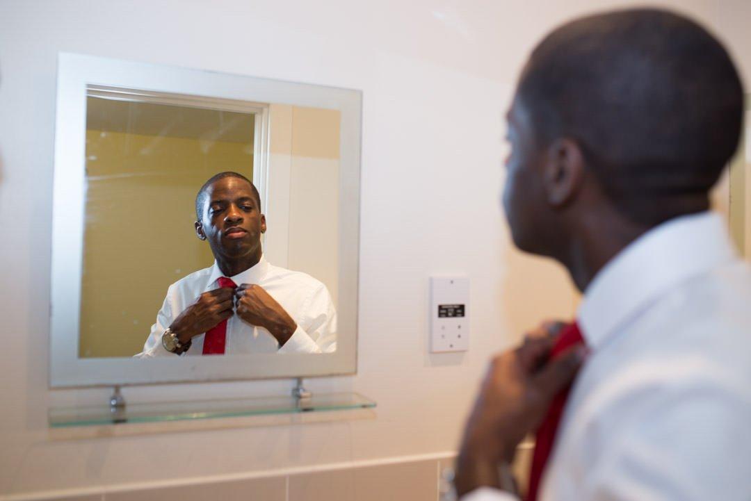 Groom straightens his tie in the mirror during groom preparation