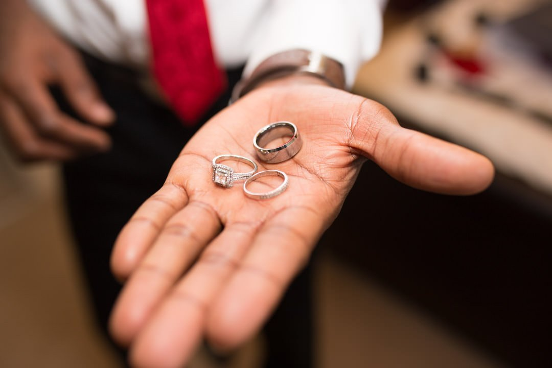 Groom holds out his hand to show the rings ready for the wedding