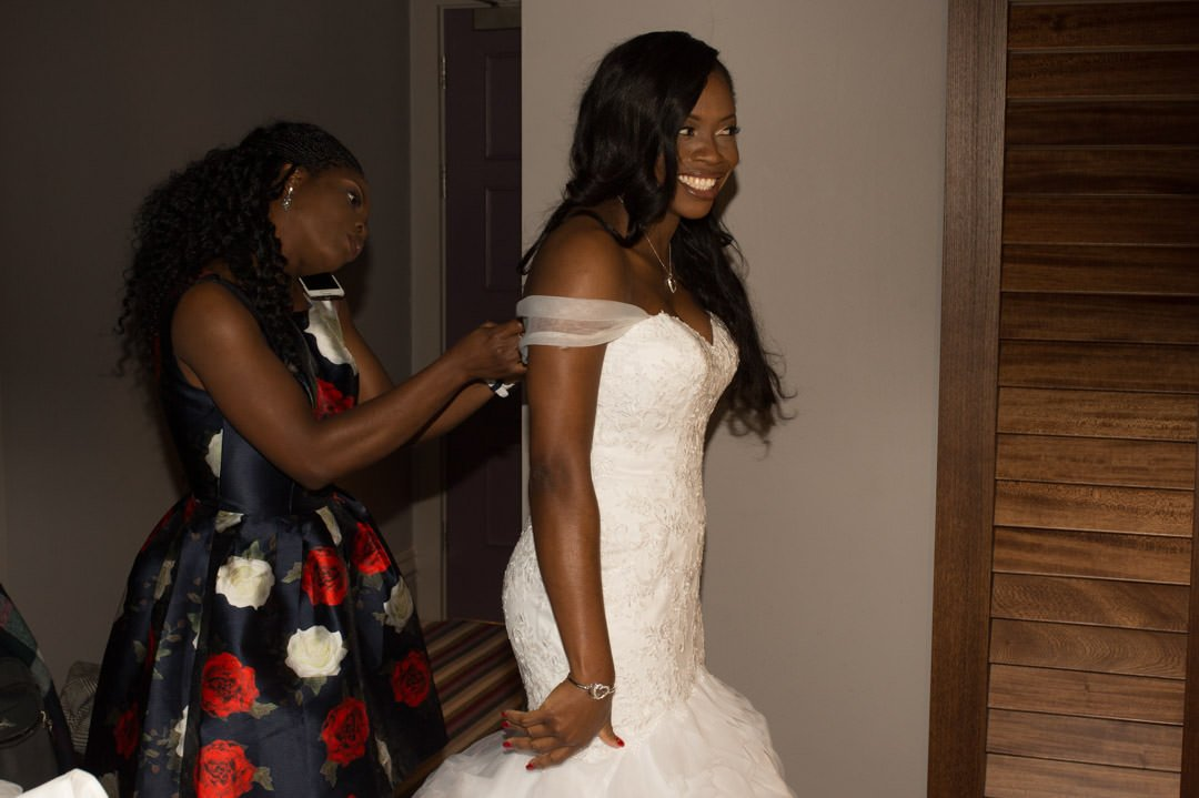 Bridesmaid buttons up the bride's dress whilst she is on the phone