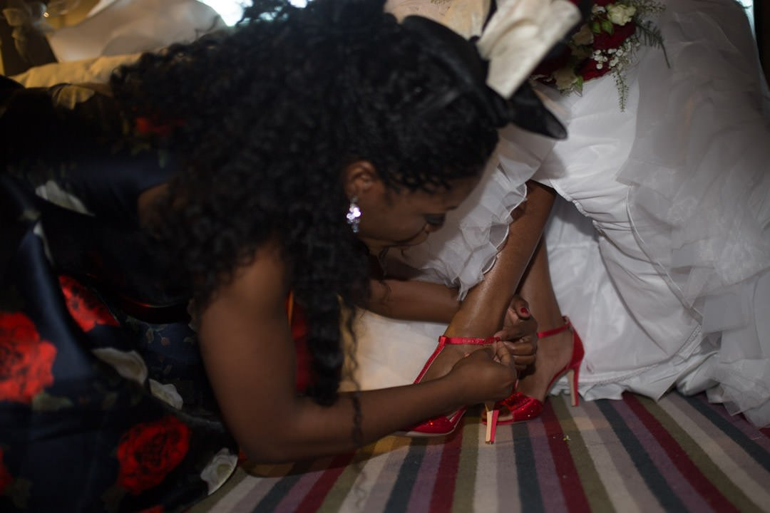 bridesmaid gets down onto the floor to do up the bride's red wedding shoes