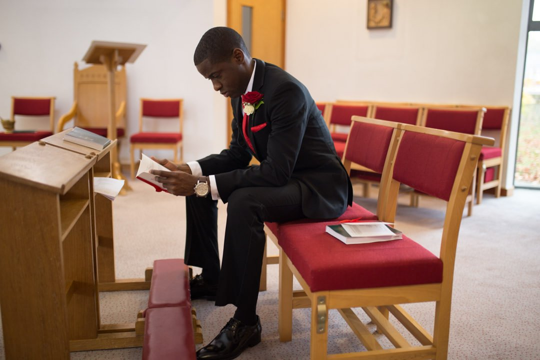 The groom reads through the order of service as he sits in the church waiting for the bride to arrive