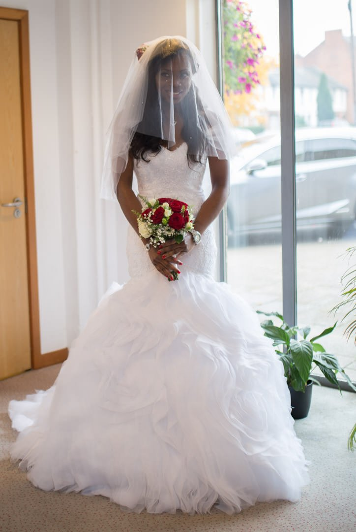 The bride stand in the modern church with her veil over her face and holding her red rose bouquet