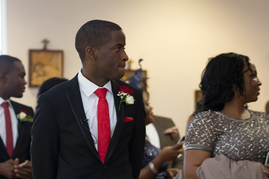 The groom looks pensive as he sees the bride arrive in the church