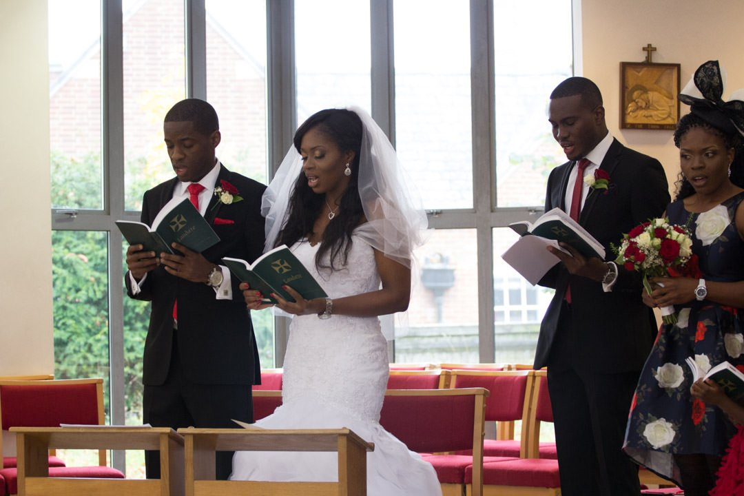 The bride and groom stand together and sing from hymn books during the church service