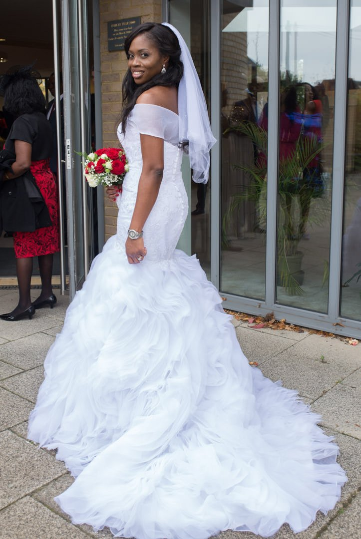 The bride looks back over her shoulder outside the church