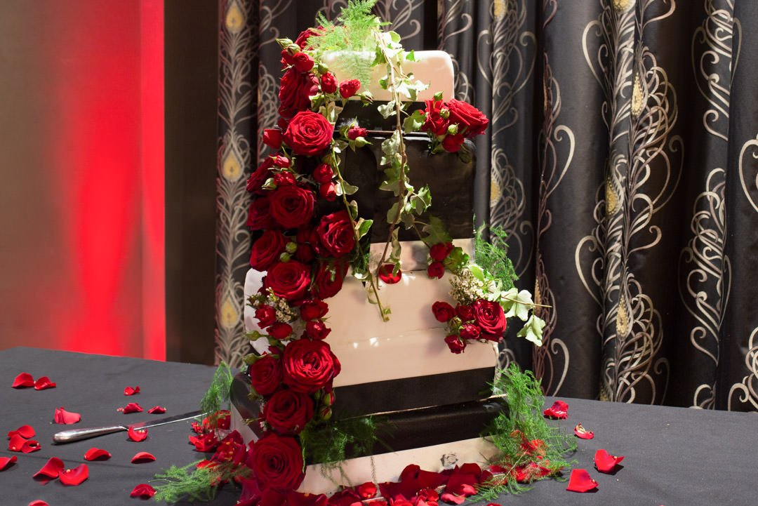multiple tiered wedding cake decorated with red roses, asparagus fern and green ivy