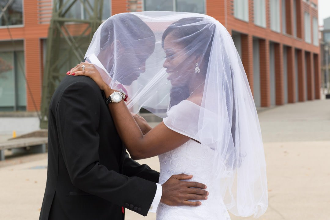 The bride and groom pose together under her veil at the aircraft hangar in Farnborough