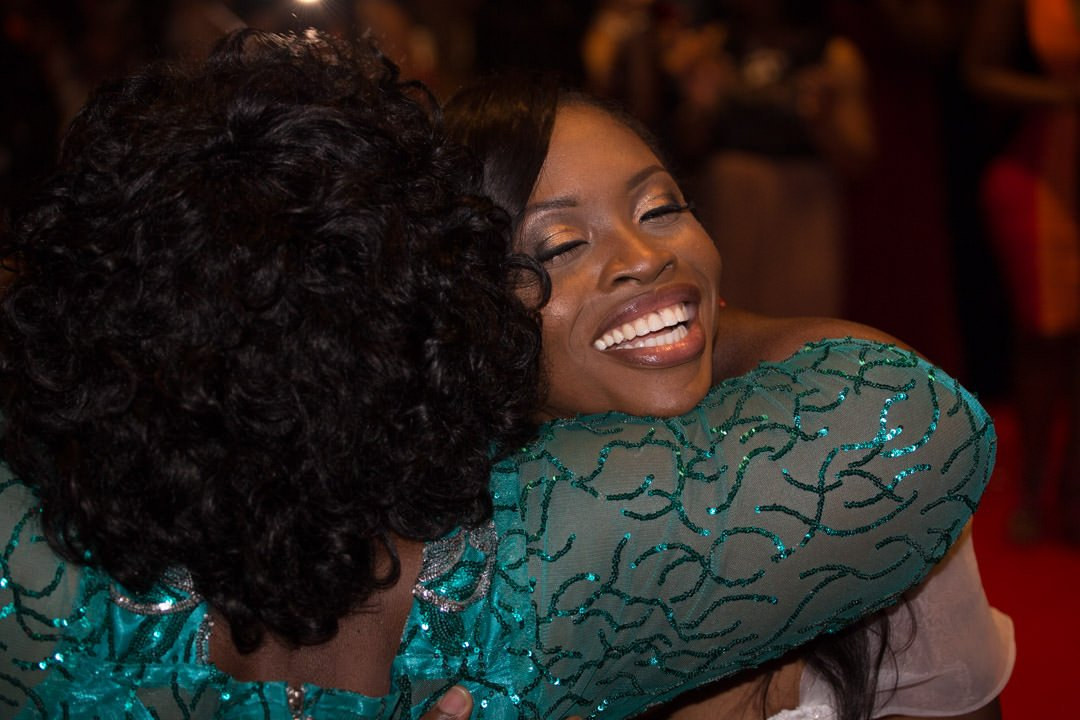The laughing bride is congratulated and hugged by a wedding guest