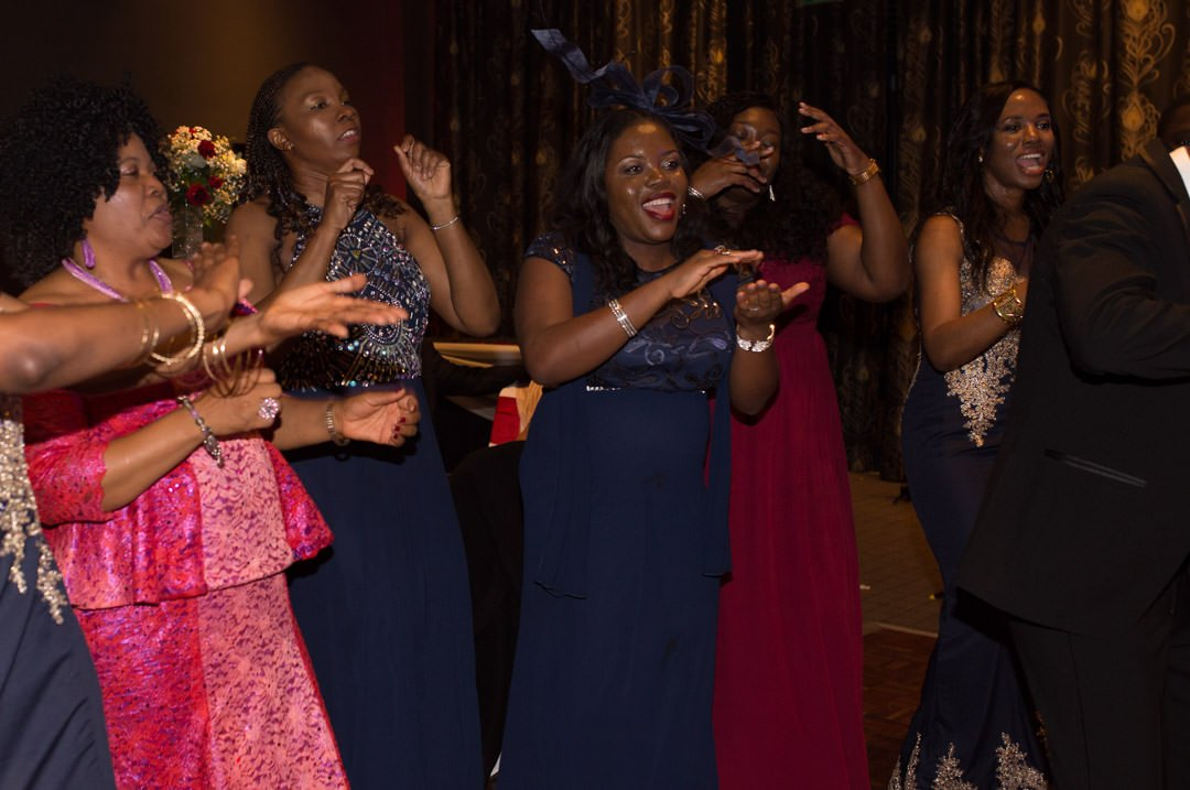 Wedding guests laugh and clap as they dance