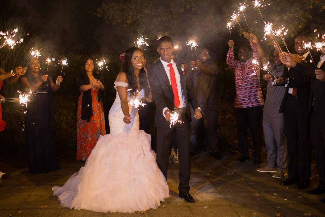 The bride and groom stand holding sparklers in a circle of their friends at the Village hotel in Farnborough