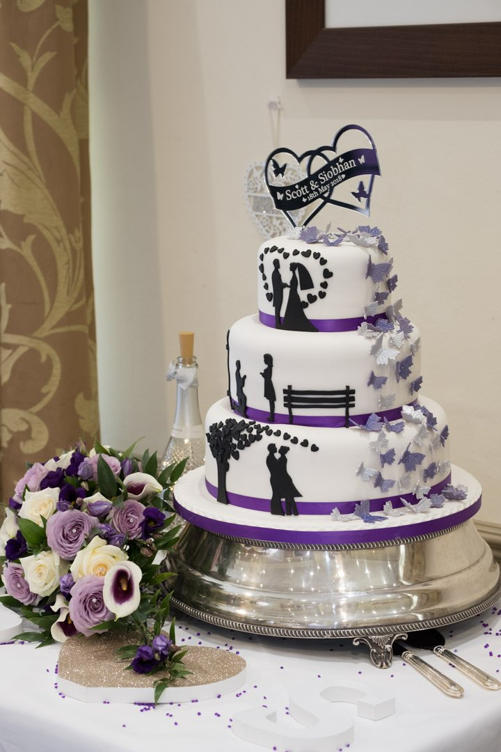 three tier wedding cake with silhouettes and purple butterflies by Jeni's cakes and flowers at Frimley Hall Hotel