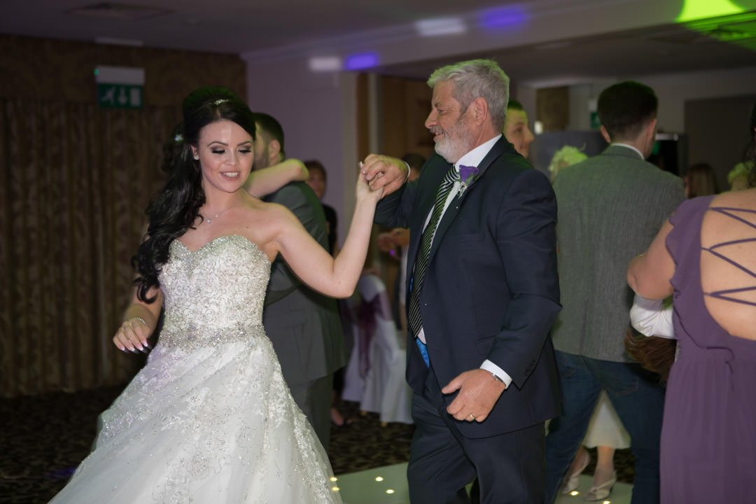 bride dances with her father in law at Frimley Hall Hotel