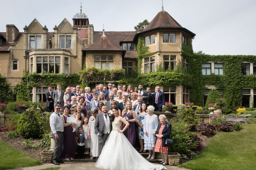 summer wedding party in front of Frimley Hall Hotel