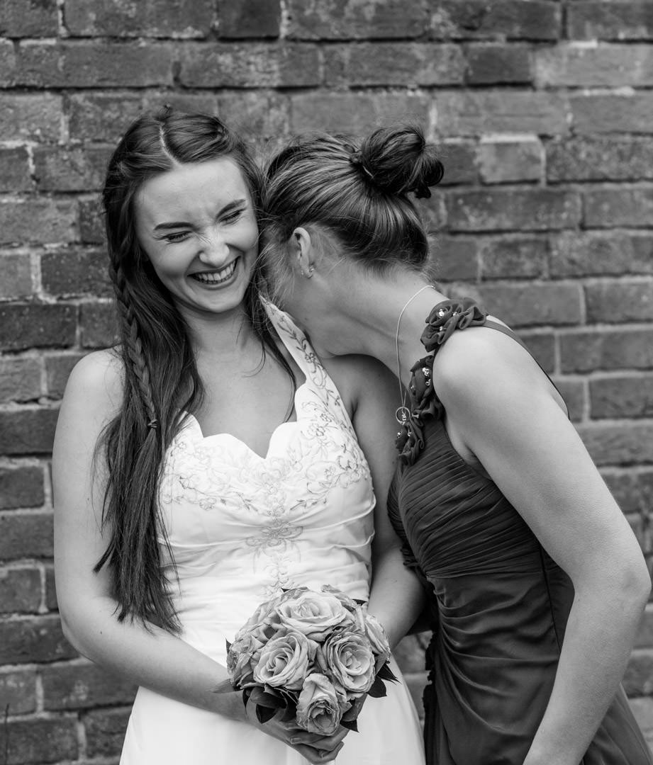 Black and white photo of a bride and bridesmaid laughing together, the bridesmaid hides her face on the bride's shoulder