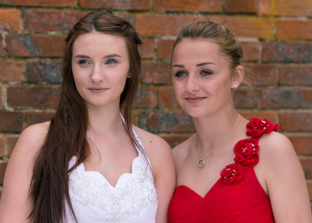 Bride and bridesmaid wearing a red off one shoulder dress, look into the distance at Warbrook House