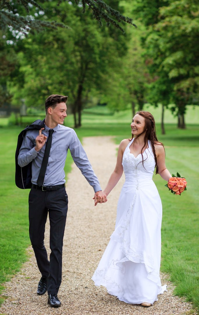 Bride and groom walk hand in hand down a path and look at each other