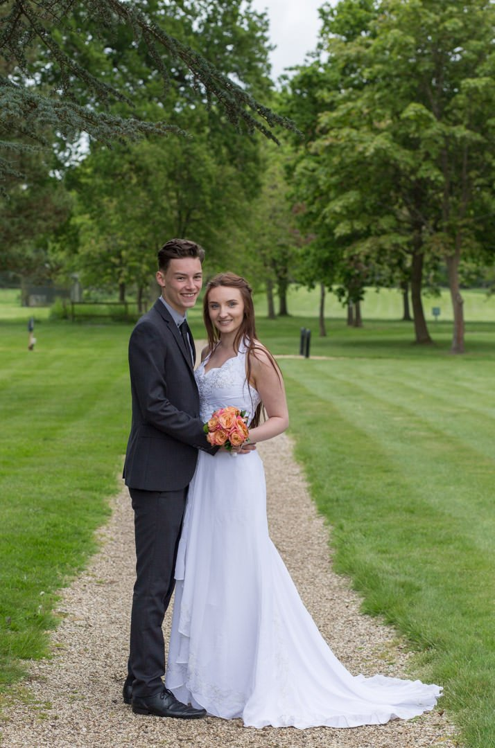 Bride and groom stand together at the end of a path at Warbrook House