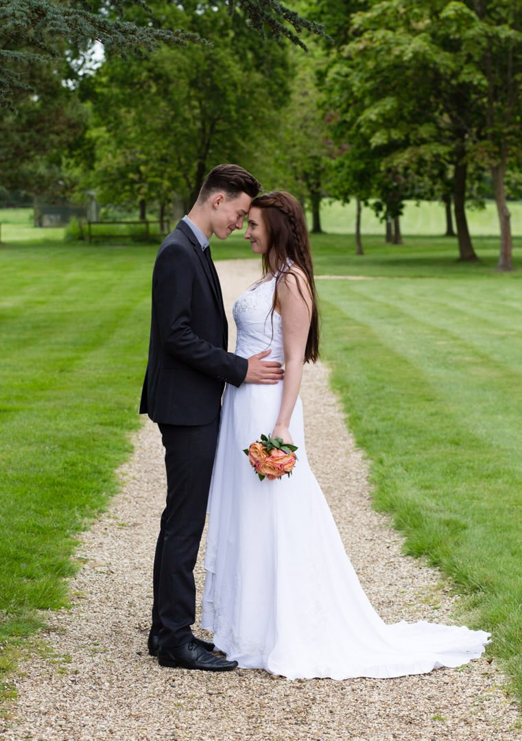 Bride and groom stand at the end of a path with heads touching at Warbrook House