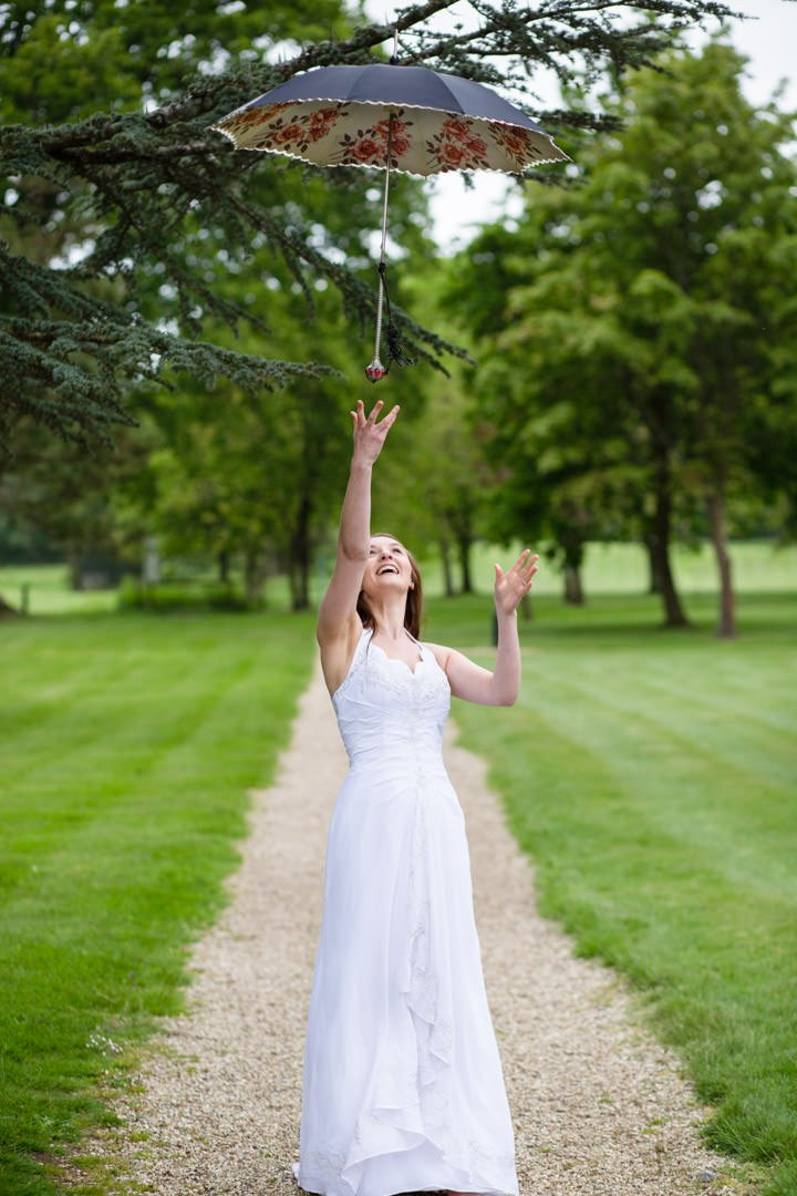 Bride stands at the end of the path and throws her parasol up in the air at Warbrook House