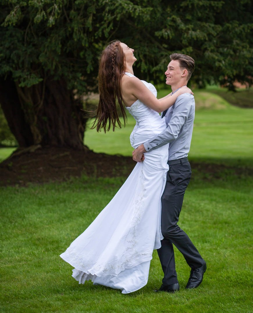 Groom picks up bride and swings her around at Warbrook House