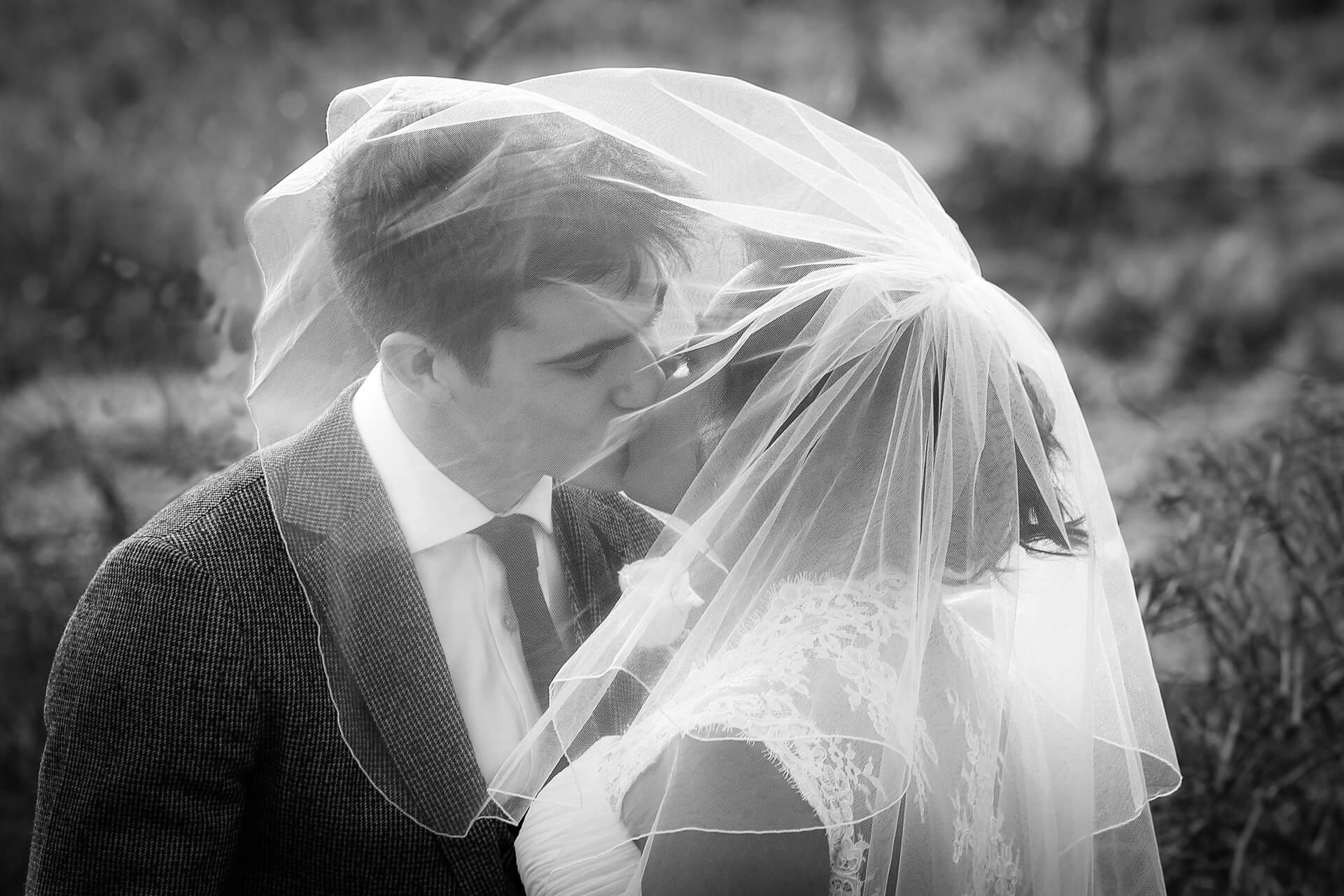 Bride and groom kiss under her veil at Waverley abbey near Farnham