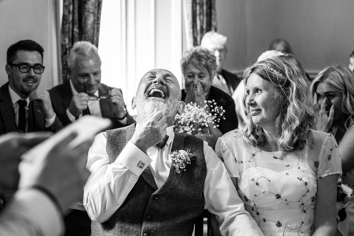 Laughing groom during wedding speeches at Monk Coniston
